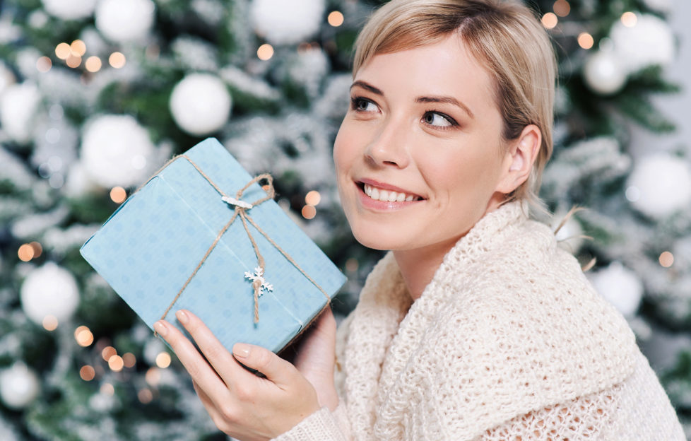 Lady holding xmas gift by the tree Pic: Istockphoto