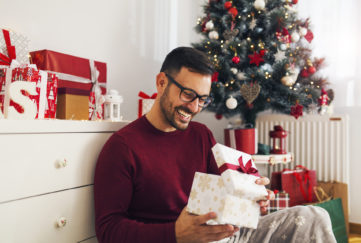 Smiling young man opening Christmas gift at home Pic: Istockphoto