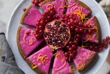 Gingerbread cake with bright pink icing, cut into 8 pieces, decorated with orange zest, berries and pomegranate seeds