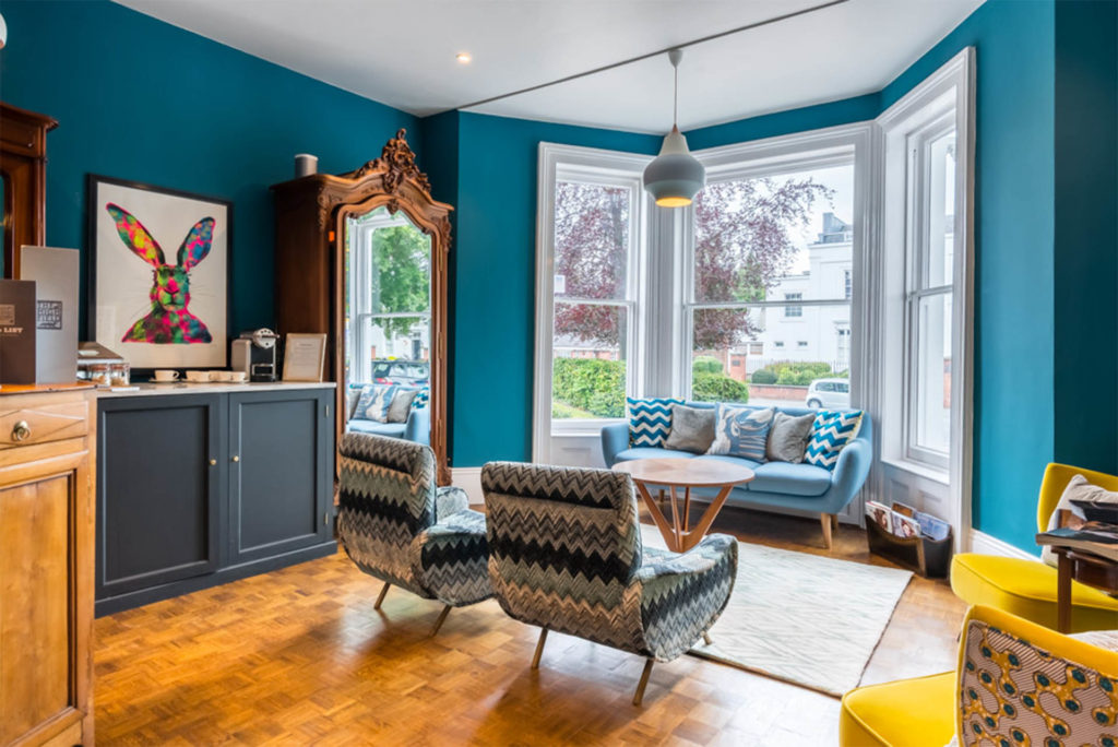 Reception area at The Town House, teal walls, warm honey flooring, funky sofa in traditional bay window