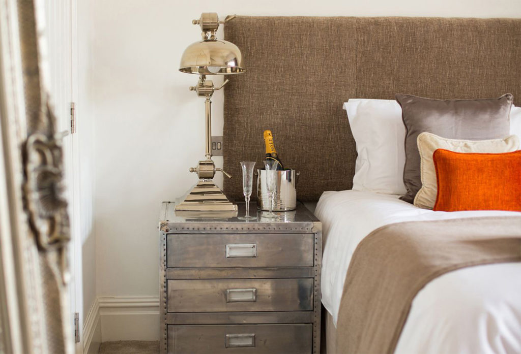 Upmarket hotel bed and bedside drawers with steampunk style lamp and champagne chilling in silver bucket. Perfect for visiting Cardiff Christmas Market