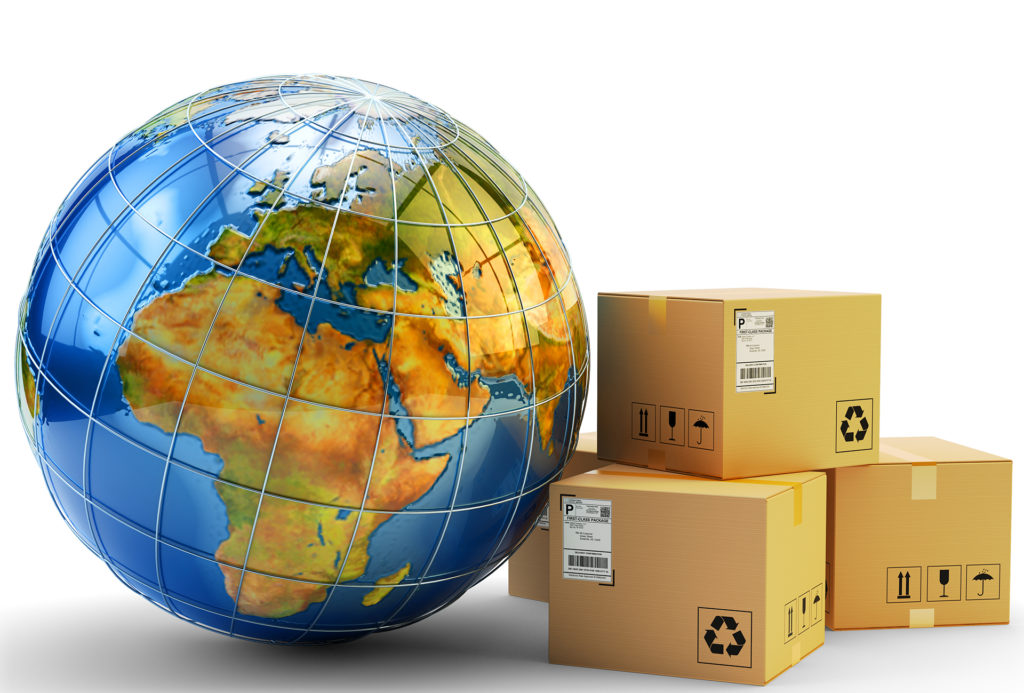 Model globe leaning against stack of 3 large parcels in cardboard boxes