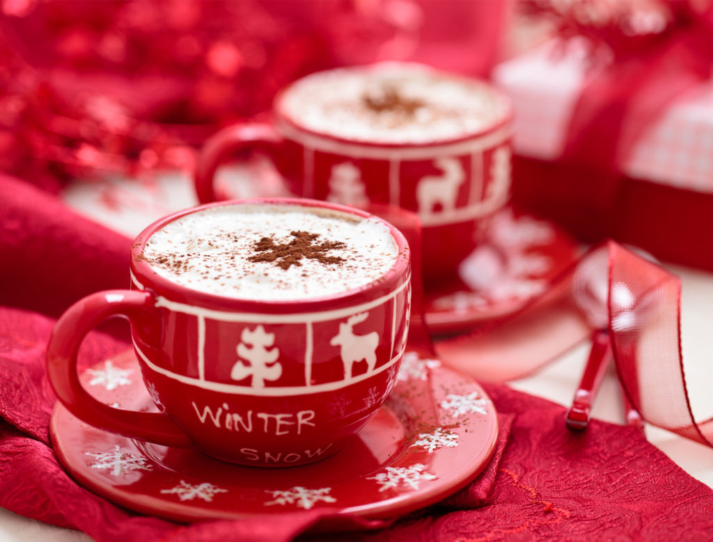 Red and white Christmas cups and saucers filled with gingerbread latte