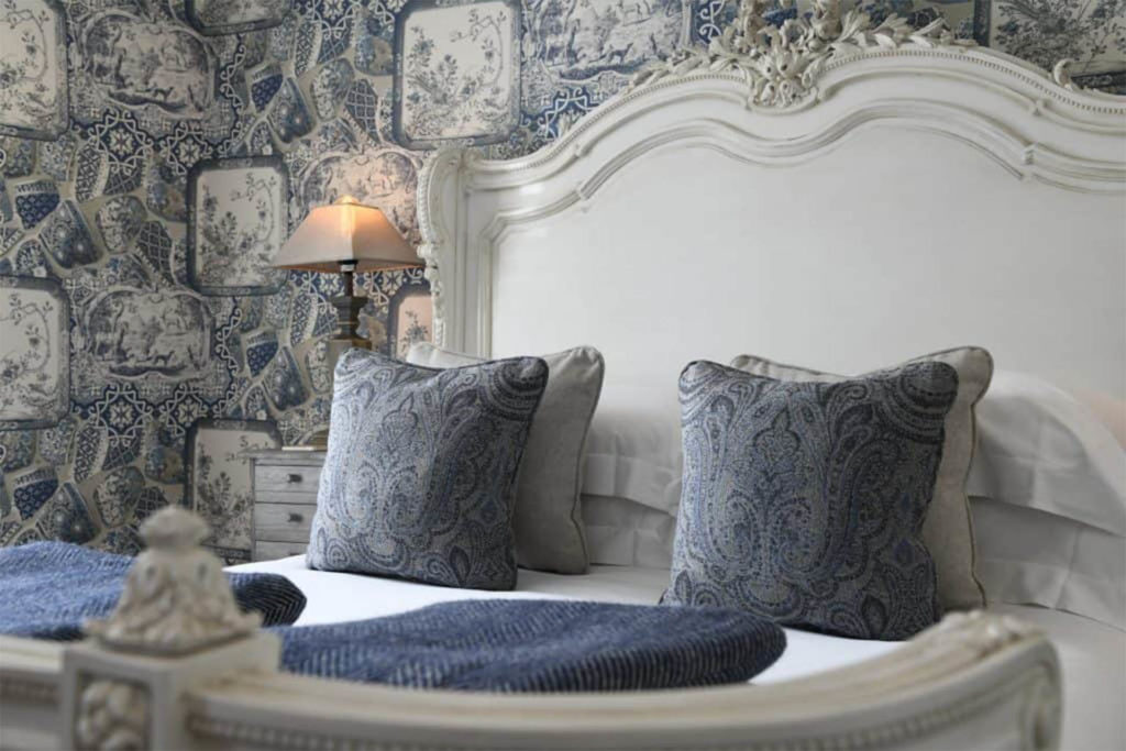Ornate cream-painted wooden bed headboard with cream and dusky blue cushions and wallpaper, Padstow Town House hotel