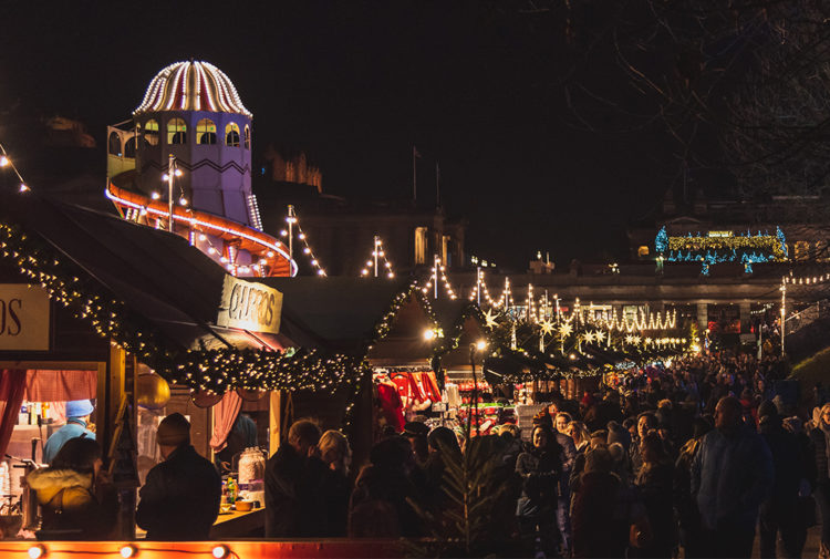 Edinburgh Christmas Market at night with lit wooden cabins, helter skelter and happy crowds