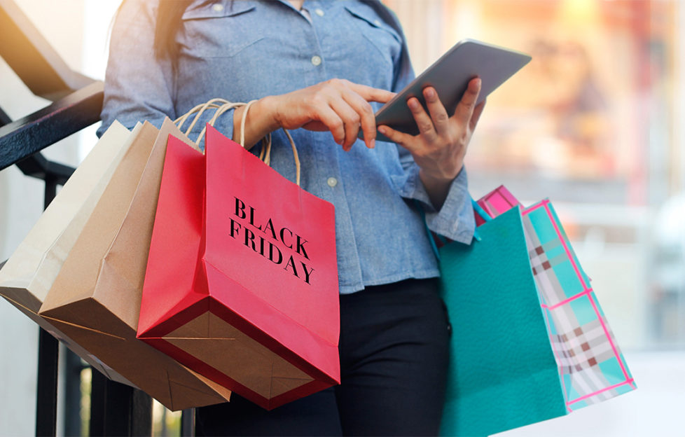 Woman with many shopping bags checks prices on tablet on Black Friday