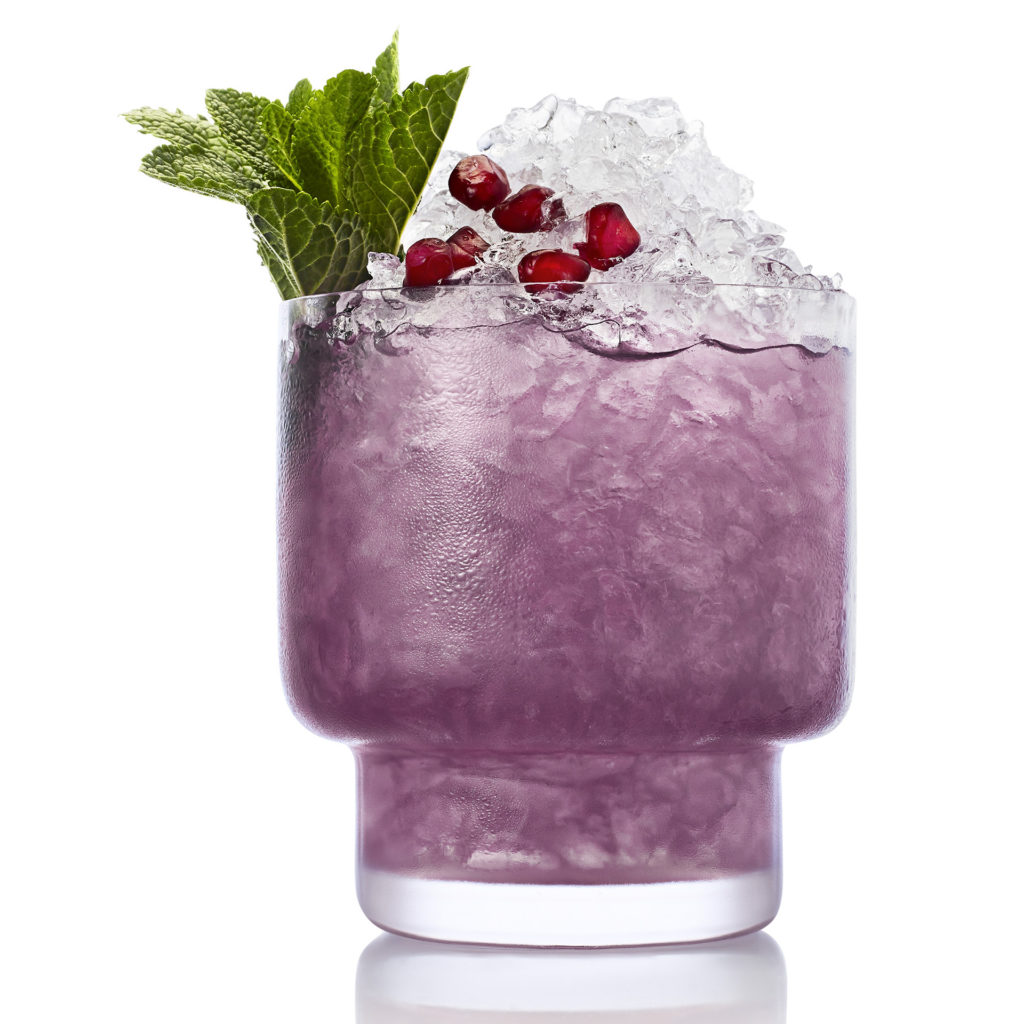 Glass filled with crushed ice and purple drink, garnished with mint and berries