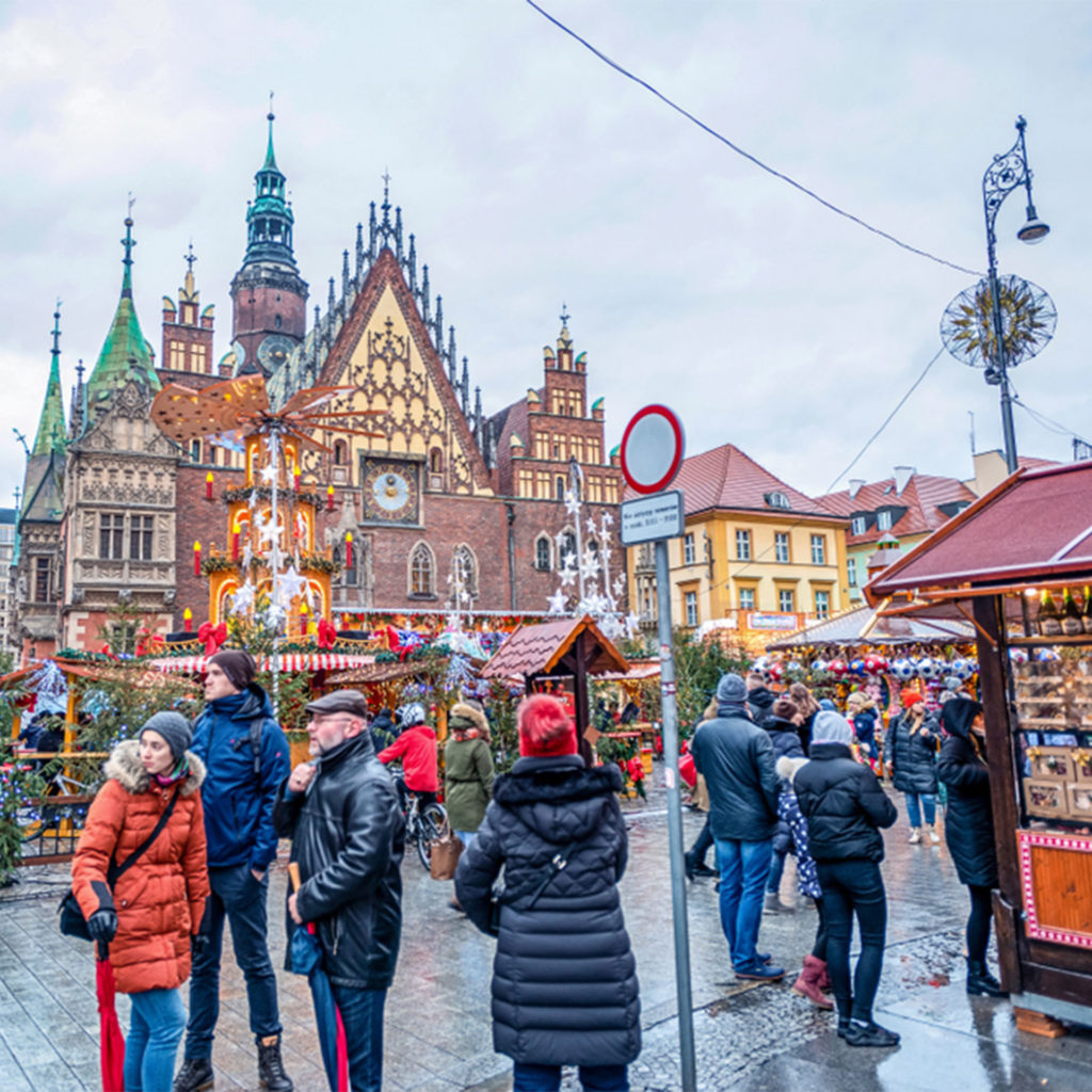 Ornate architecture, spires and gables, with stalls, lights and visitors