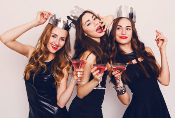 Three young women in black party dresses and silver paper hats, drinking cocktails