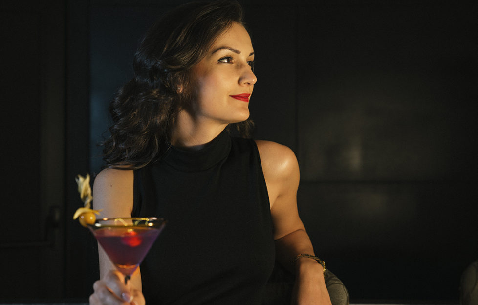 Smiling, relaxed elegant woman in black dress and lipstick, holding red mocktail in conical glass