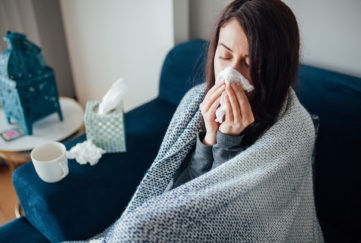 Sick woman blowing her nose, she covered with blanket