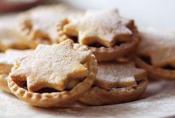 Mince pies with star shaped lids on a plate