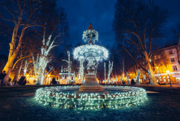 Fairylit fountain at night, trees and floodlit classical architecture