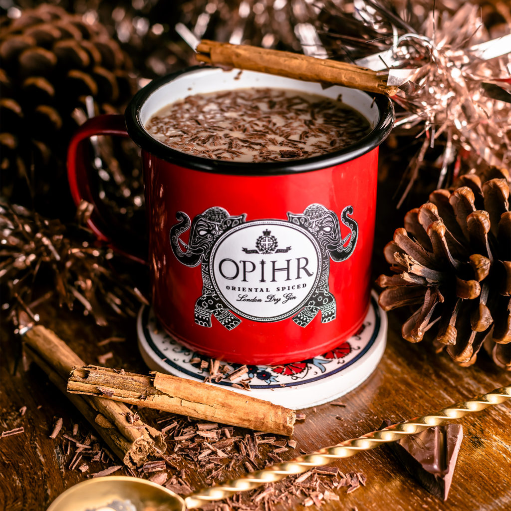 Mug of Moon Milk Punch, surrounded by cinnamon stocks, pine cones and chocolate shavings