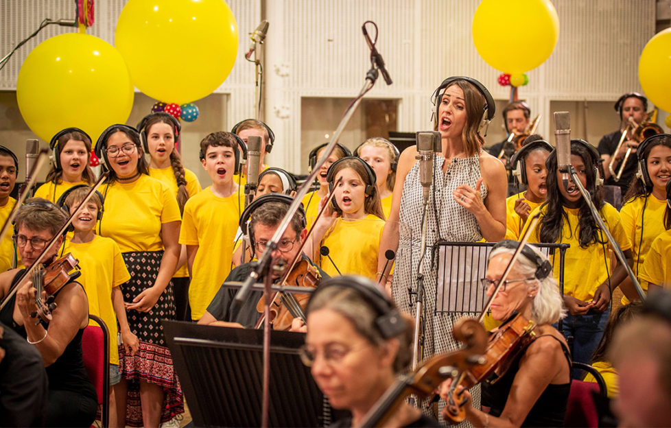 Suranne Jones recording vocal with orchestra members and children's choir in yellow t shirts