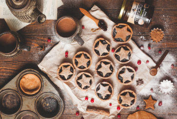 10 star-topped mince pies, cranberries scattered over, cinnamon stick, jar of Meridian almond butter, earthenware teapot and mug of tea on side