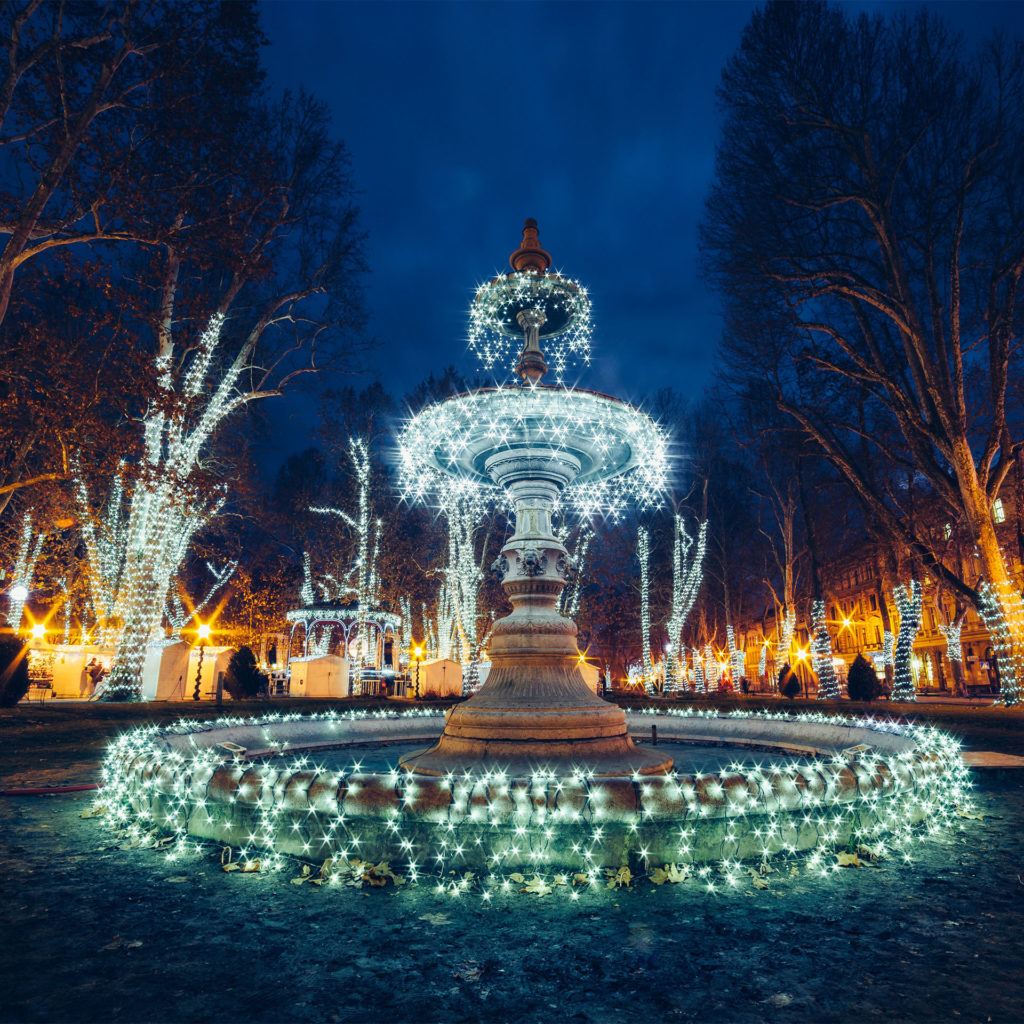 Fairylit fountain in the dark, floodlit classic buildings (same as featured image)