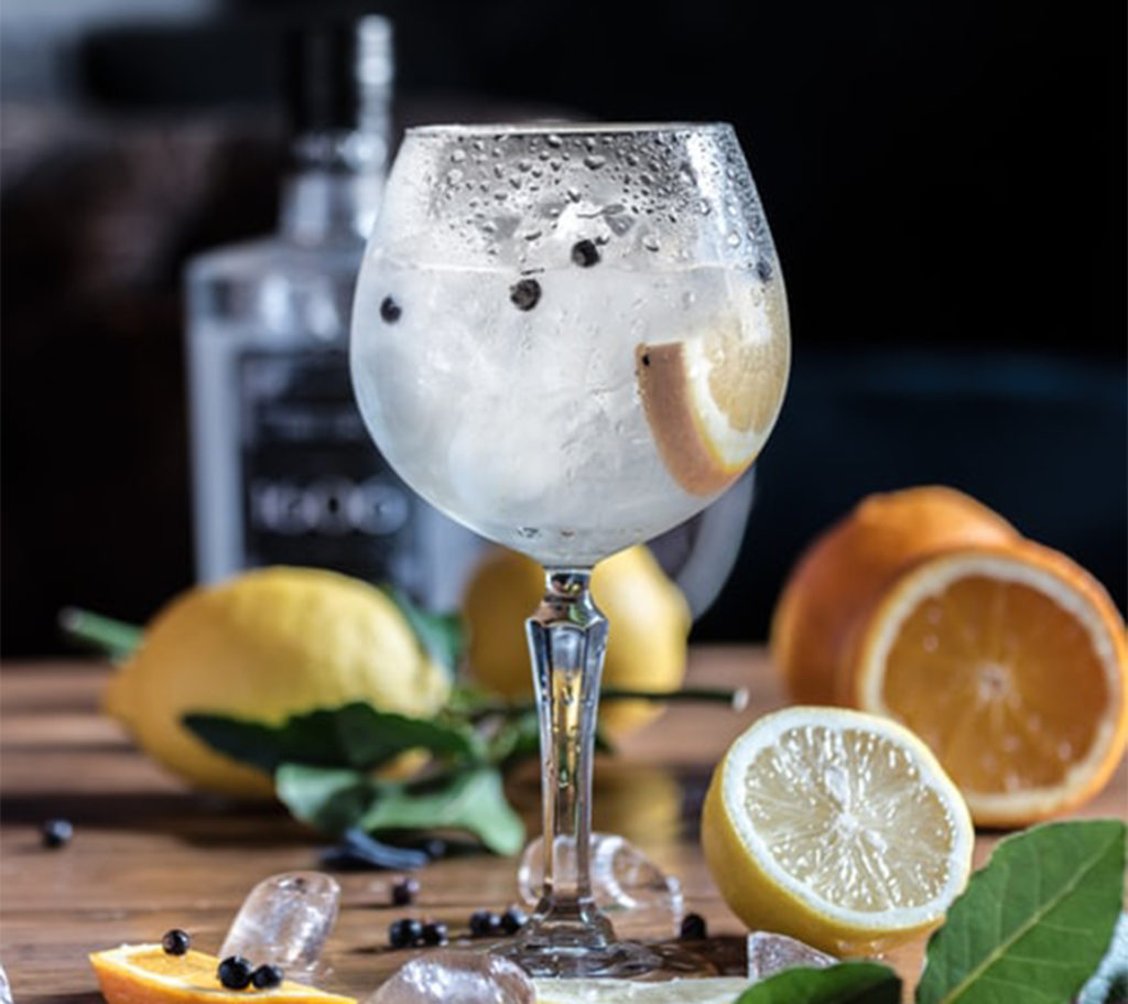 Large glass of gin with cut lemons, ice cubes and leaves scattered around