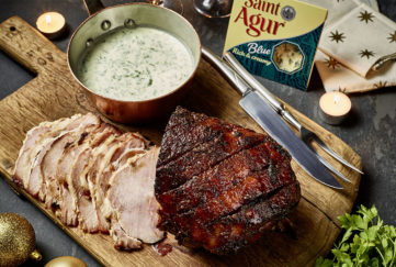 Brown caramelised glazed ham, cut into slices on wooden board, bowl of Saint Agur blue cheese dressing on the side