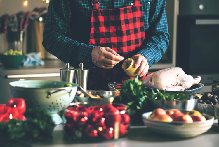 Middle aged man about to spread mustard on raw turkey, vegetables waiting to be prepared in foreground