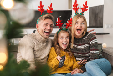 Cheerful family sitting together on a couch at the living room at Christmas