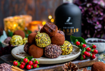 Plte of gorgeous truffles coated in pistachios and cocoa in a pyramid on a plate, one with a bite taken, berries, pine cones and cassis bottle